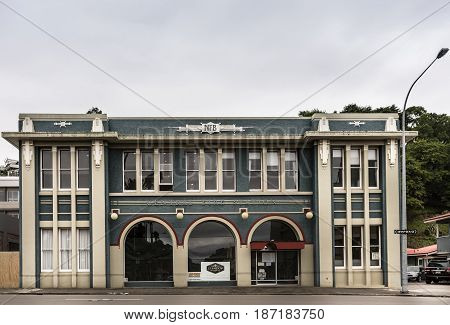 Napier New Zealand - March 9 2017: Historic Union Fire Station is a rectangular green and white building in art deco style. Now an office building. Street scene under silver sky.