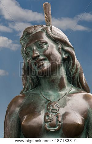 Napier New Zealand - March 9 2017: Closeup of the face of the iconic Maori symbol Pania of the Reef. Bronze statue in the beach park against blue sky with a few white clouds.