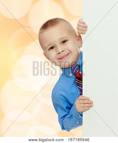 Beautiful little boy in a blue shirt and tie peeking from behind the banner.Brown festive, Christmas background with white snowflakes, circles.