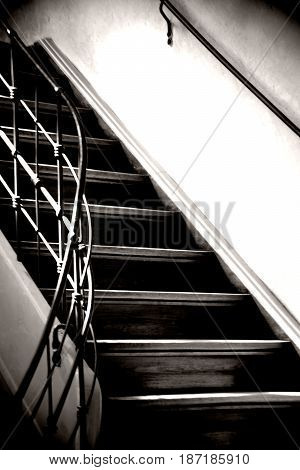 Light falls on the narrow staircase of a house floor with wooden steps.