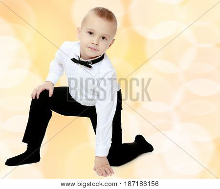 Elegant little boy in black pants , white shirt and black tie. Standing on one knee.Brown festive, Christmas background with white snowflakes, circles.