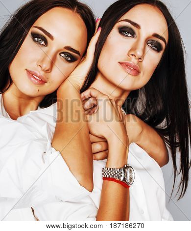 two sisters twins posing, making photo selfie, dressed same white shirt, diverse hairstyle friends bright makeup