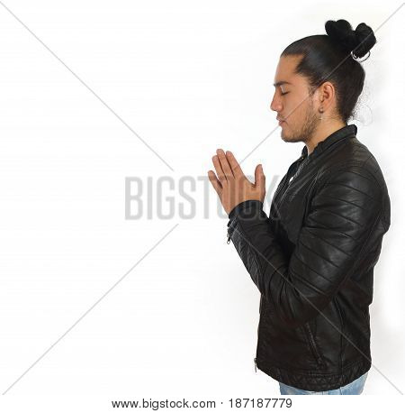 Young hispanic man with gathered hair done bow dressed in black shirt and black leather jacket, with his hands clasped in prayer position, seen in profile