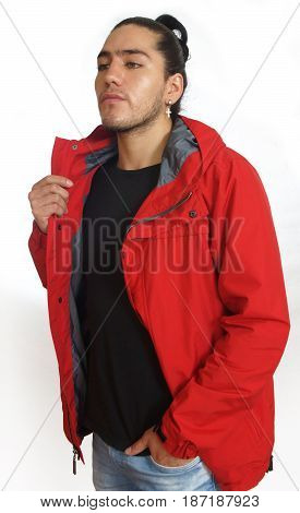 Young hispanic man with gathered hair done bow wearing black t-shirt and red jacket, with one hand on his pants pocket, looking left