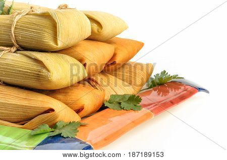 Tamales Mexican dish made with corn dough chicken and chili wrapped with a corn leaf