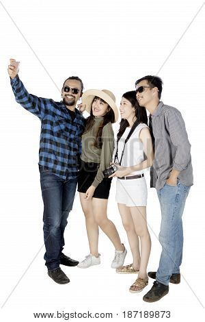 Image of an Afro man using a mobile phone for taking a picture with his friends isolated on white background