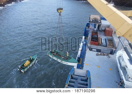 Unloading cargo into barges from a small ship.