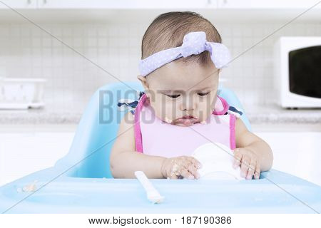 Portrait of attractive female baby sitting on a high chair while eating puree with a bowl in the kitchen