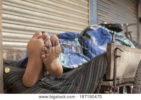 bare foot of sleeping homeless man in bike cart in Delhi city India