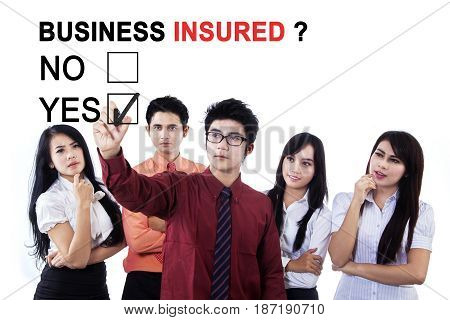 Image of business team selecting a yes option with text of business insured on the whiteboard