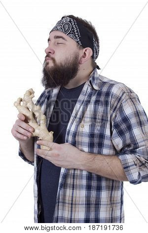 Bearded farmer with the root of ginger in the hands of