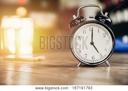 5 O'clock Time Retro Clock On Wood Table With Sun Light Background