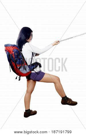 Full body of a young female backpacker dragging something with a chain in the studio while carrying a rucksack isolated on white background