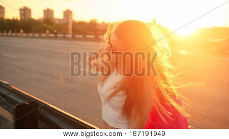 Young attractive hipster girl hitchhiking sits on the highway fence and holds a bouquet of lilac flowers. She is dressed in top and jeans. Backlight photography. The setting sun plays in her hair.