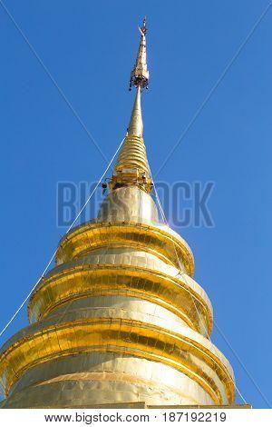 Closeup Zoom Thai Asian Style Golden Pagoda Against Clear Blue Sky.