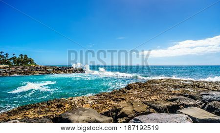 Waves breaking on the barriers of the lagoons at the resort community of Ko Olina, on the West Coast of the Hawaiian island of Oahu, and making the blue waters of the lagoons a safe place to swim