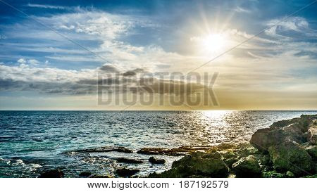 Sunset over the horizon with a few clouds on the rocky shores Paradise Cove on the west coast of the tropical Hawaiian island of Oahu