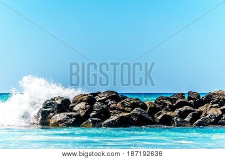 Waves crashing on the barriers made of large rocks at the resort community of Ko Olina on the West Coast of the Hawaiian island of Oahu. The barriers make the lagoons safe for swimming