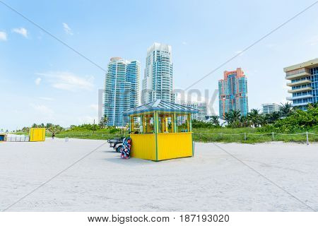 Miami high rise behind colorful little yellow and blue beach kiosk Florida USA.