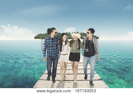 Group of happy multi ethnic friends walking on the wooden pier while laughing and embracing to each other