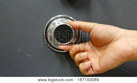 Close up of a safe lock and male hand conceptual image