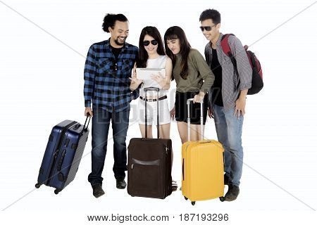 Group of young people looking at digital tablet together while holding suitcase isolated on white background