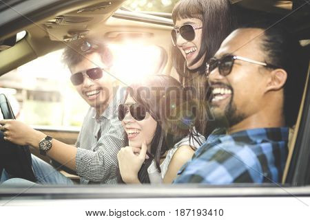 Multiracial group of young people wearing sun glasses smiling together while sitting in the car