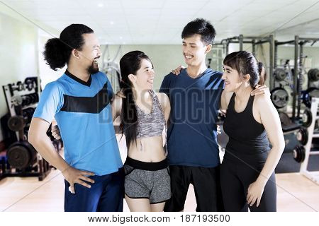 Multi ethnic group of young people wearing sportswear standing at the gym while smiling together