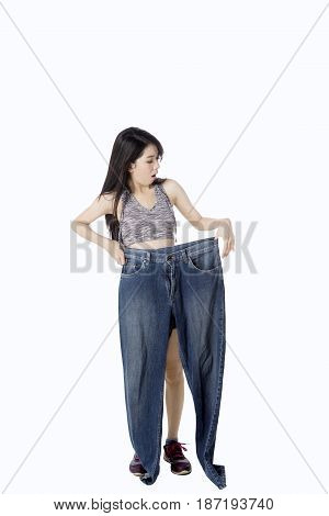 Diet concept. Successful woman doing diet and holding her old jeans in the studio isolated on white background