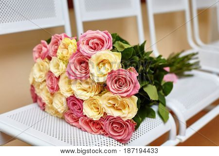 Large flower bouquet of yellow and pink roses on white metall chairs