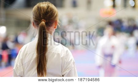 Back view of young gymnasts in white Kim, who is in the frame back on the Mat on the background of groups of children - young athletes, in the gym.