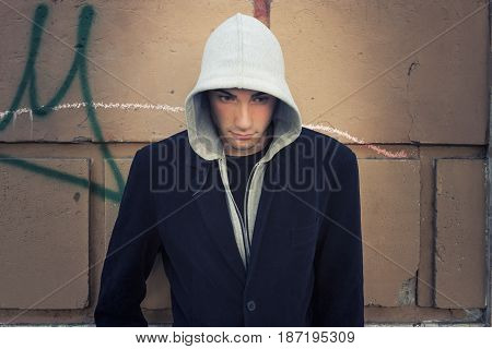 Cool man model with hoodie, wall background. Young Man with hoodie in front of a wall. The handsome guy wearing a light jacket and a gray sweatshirt.