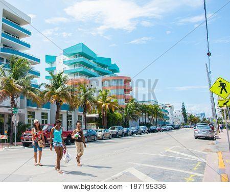 Miami, USA- June 28, 2016; Three Afro-American modern women cross street from shops in Miami Florida USA.