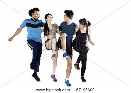 Multiracial group of friends exercising while laughing together isolated on white background