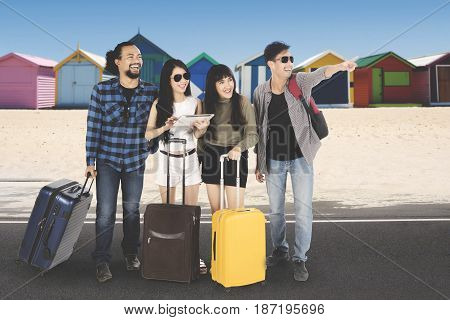 Portrait of happy multiracial group of friends standing on the beach street while looking at something with their luggage shot with beach huts background