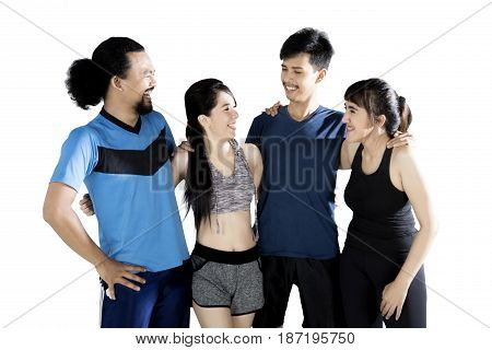 Multiracial group of sports people laughing together while standing in studio isolated on white background