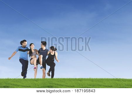 Group of joyful multiracial people doing workout together while jumping and laughing