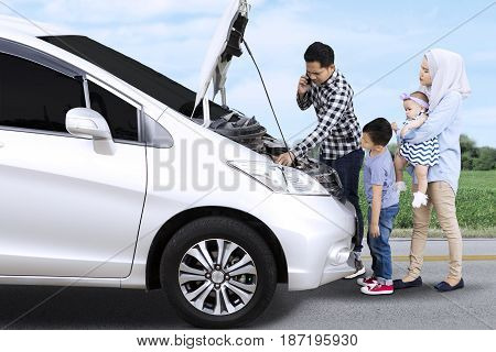 Muslim family having problem with their broken car while standing on the street