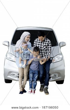 Portrait of Muslim family using a digital tablet while sitting on the hood of their car isolated on white background