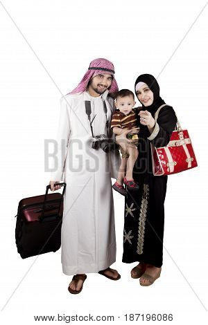 Image of Muslim family carrying a suitcase and a digital camera while pointing at something in the studio