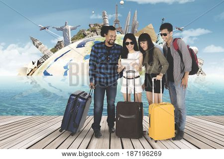 Multiracial group of young people looking world map on digital tablet with famous landmark background