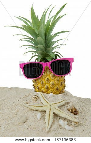 Pineapple fruit on the sand with sun glasses starfish and seashells. Isolated on white background
