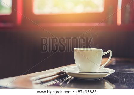 Single White Cup Of Espresso Hot Coffee With Morning Sun Light From Windows Background On Wooden Gla