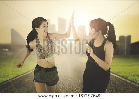 Multi ethnic sports women giving high five while doing jogging together on the street