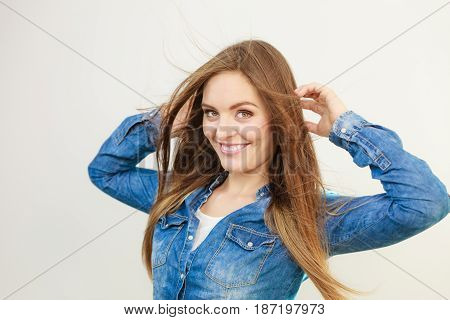Young girl with waving hairs. Cheering woman standing in wind. Fashion coiffure leisure lifestyle concept.
