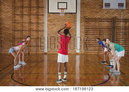 High school boy about to take a penalty shot while playing basketball in the court