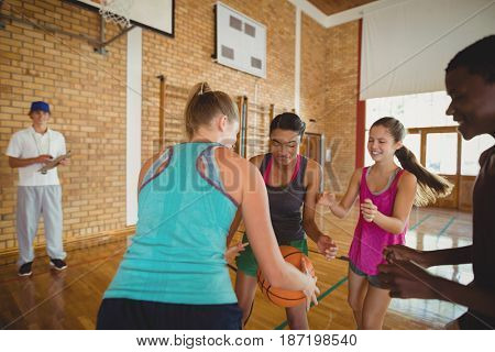High school team playing basketball in the court