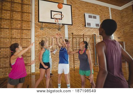 High school team scoring a goal while playing basketball in the court