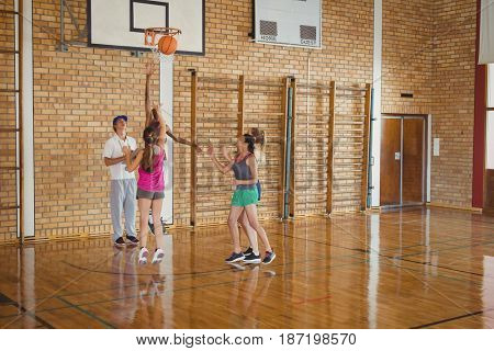 Smiling high school team defending while playing basketball in the court