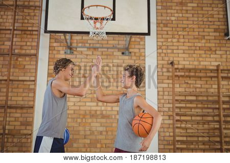 High school boys with basketball giving a high five in the court